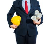 engineer yellow helmet for workers security with construction plans isolated - stock photo
