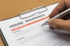 man signing a house insurance policy - stock photo