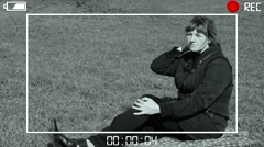 Woman sitting on green grass. Simulation through the viewfinder - stock footage