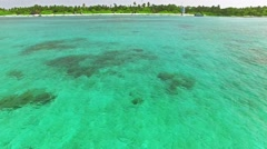 Flying over water, stone and sand beach in the Maldives. Stock Footage