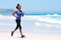 Healthy young female running on the beach - stock photo