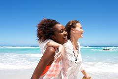 Smiling young female friends at the beach - stock photo