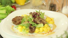 Salad with chicken liver and mango - stock footage