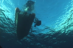 Distant scuba diver exiting on water surface in Vanuatu, UP7379 Stock Footage