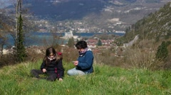 A mother and daughter sitting in a meadow, Lake Annecy in the background Stock Footage