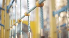 Child walks on a suspension bridge on playground Stock Footage