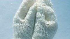Female hands in mittens with heart on snow background Stock Footage