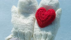Female hands in mittens with heart on snow background. - stock footage