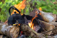 Burnt kettle on campfire - stock photo