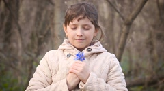 Girl collects blue snowdrops in the forest Stock Footage