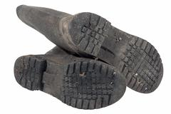 Tread Pattern on Sole of Dirty Wellington Boots - stock photo