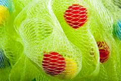 Closeup of Green Bath Puff with Red and Yellow Baubles - stock photo