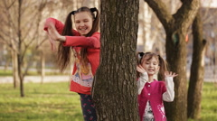 Cheerful girl playing hide and seek behind a tree - stock footage