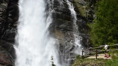 Tourist taking picture of waterfall at Lillaz, Gran Paradiso NP, Alps, Italy Stock Footage