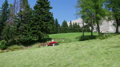 Man in a lawn mower tractor cutting off the tall grasses Stock Footage