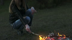 Girl puts branches on the fire Stock Footage