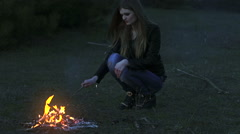 Young woman with a stick mixes the ashes in the fire - stock footage