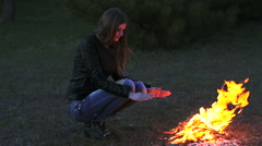 The girl heated by the fire and watching the flames - stock footage