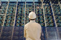 Hispanic technician examining power grid infrastructure - stock photo