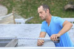 Deaf Caucasian roofer measuring skylight on roof Stock Photos