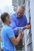 Deaf Caucasian homeowner signing to repairman Stock Photos