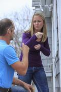 Caucasian homeowner signing to deaf repairman Stock Photos