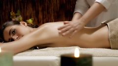 Masseuse putting oil on back of woman in spa starting massage 4K Stock Footage