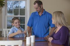 Caucasian family signing at dinner table - stock photo