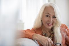 Caucasian woman smiling on sofa Stock Photos