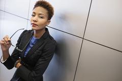 Mixed race businesswoman holding eyeglasses Stock Photos