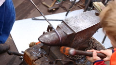 A blacksmith models a bar of iron with hammer after took it from fire forge. Stock Footage