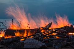 Campfire at twilight on beach - stock photo