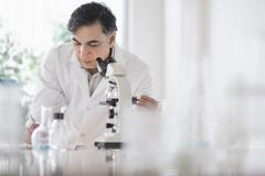Mixed race scientist using microscope in laboratory Stock Photos