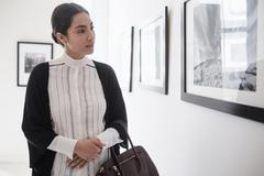 Hispanic woman admiring art in gallery Stock Photos