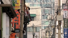 Man fixes electrical wires at the pole in Seoul, Korea. - stock footage