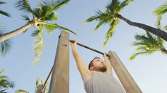 Fitness man working out pull-ups on chin-up bar - young fit man cross training - stock footage