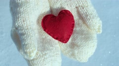Female hands in mittens with heart on snow background - stock footage