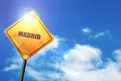 Yellow road sign with a blue sky and white clouds: madrid - stock illustration
