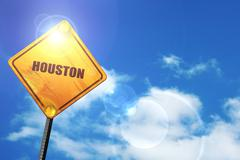 Yellow road sign with a blue sky and white clouds: houston - stock illustration