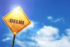 Yellow road sign with a blue sky and white clouds: delhi - stock illustration