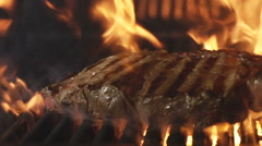 Beef steak on a grill in a fire. Slow motion - stock footage