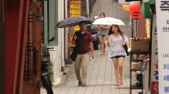Asian people walk with umbrellas by the Insadon street in Seoul, Korea. Stock Footage
