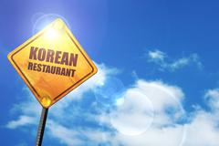 Yellow road sign with a blue sky and white clouds: Delicious kor - stock illustration