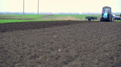 Agricultural tractor plows soil and plantings of agricultural cultures Stock Footage