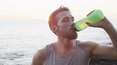 Fitness man drinking water after running exercising in summer on beach Stock Footage