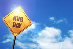 Yellow road sign with a blue sky and white clouds: hug day - stock illustration