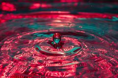 Beautiful colorful water splash from fallen drop Stock Photos