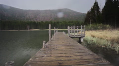 Steady shot on the lake pier in the rain with water drop on the lense Stock Footage