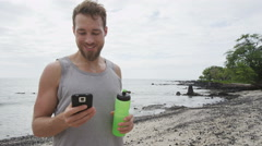 Fitness man looking at phone app on beach smiling happy after workout Stock Footage