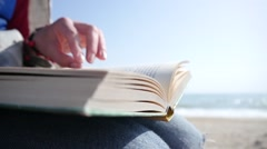 Female reading a real paper book leafing pages relaxing at a sea shore sand Stock Footage